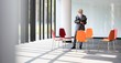 Mature businessman reading document while standing amidst chairs in new office