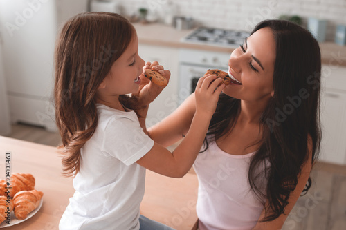 Leinwand Poster portrait of mother and daughter feeding each other with biscuits on the kitchen