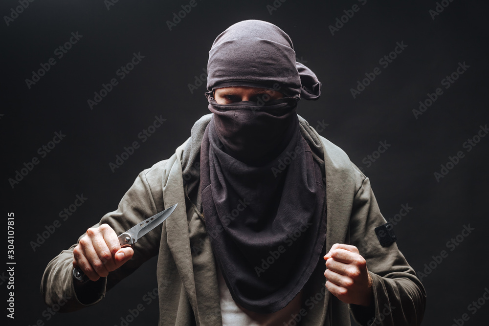 Fototapeta  criminal in a mask threatens with a knife the dark background