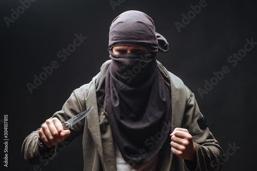 Cuadros en Lienzo  criminal in a mask threatens with a knife the dark background