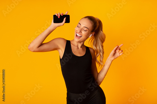 Woman In Wireless Earbuds Holding Smartphone And Dancing, Studio Shot - 304108810