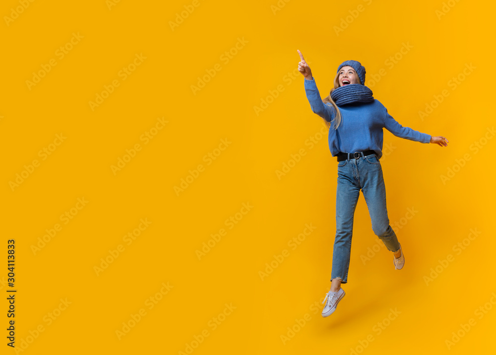 Fototapeta Emotional winter girl pointing at copy space over yellow background
