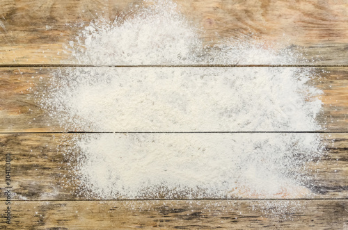 White flour on a wooden background, top view. Background with copy space - 304133810