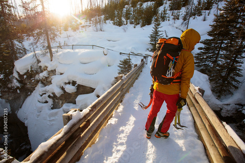 Professional alpine climber Jess Roskelley hikes back to the trailhead after a day of ice climbing at the scenic Marble Canyon, BC in Kootenay National Park near Banff, Alberta amidst the stunning backdrop of the Canadian Rockies.