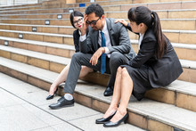 A Sad Looking Young Businessman Sitting At The Staircase Looking Down With Stressed And Depressed Look Gesture With Two Businesswomen Sitting On Both Side Comforting Him