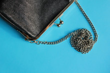 Black Women's Clutch Bag On A Chain On A Blue Background, Top View, Copy Space, Flat Lay