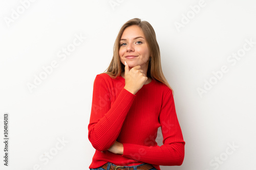 Young blonde woman with red sweater over isolated white background laughing Tablou Canvas