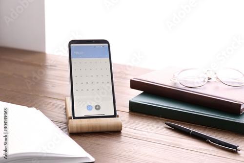 Fototapeta  Smartphone with calendar app on wooden table