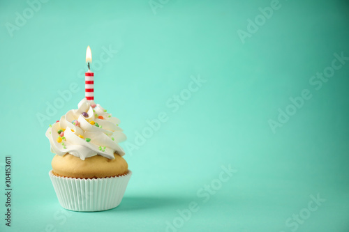 Photo Delicious birthday cupcake with candle on light green background
