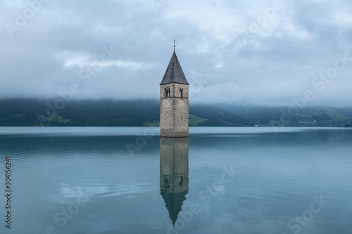 Foto Church tower of Altgraun, Reschensee on a cloudy morning in summer