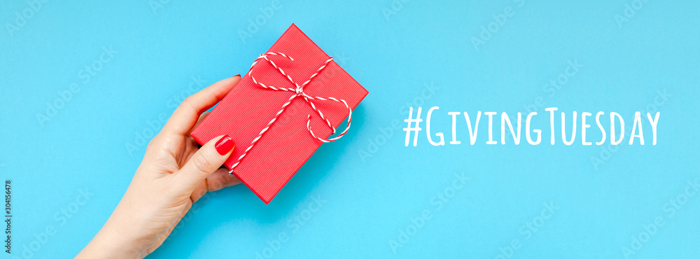 Fototapeta Giving Tuesday concept with red gift box in hand