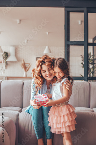 happy mother taking present from the daughter present box for mothers day at hom Fototapete