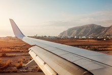 Plane Landing In Fira, Santorini Island. View Of Airplane Wing. Traveling Concept