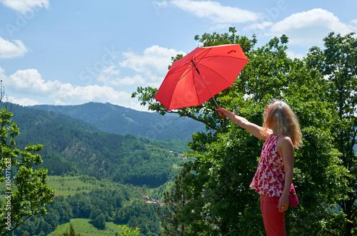 Foto auf AluDibond Blau türkis Blond woman, umbrella and landscape