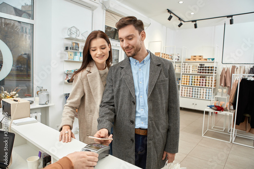Fotomural  Adult woman and man buying clothes in shopping mall