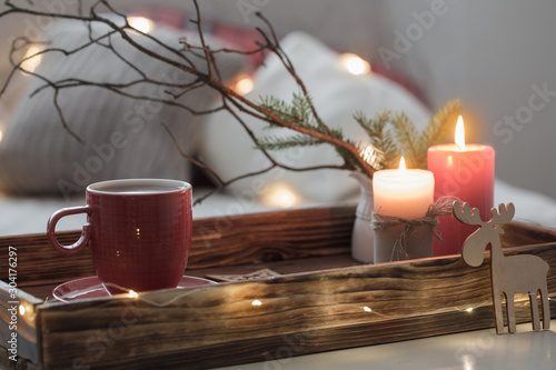 Fotomural  Red cup of tea on tray with burning candles on background sofa with pillows