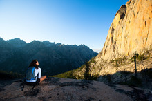 A Woman Enjoys The Dramatic View Of A Sunlit Elephant's Perch, A 1200  Foot Wall In The Sawtooth Mountains Popular For It's Climbing Routes. The 'Perch' Sits Near The Beautiful Saddleback Lakes. The Whole Area Is So Stunning It Has Earned The Nickname 'Shangrila.