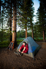 A Man Puts On His Hiking Boots After Setting Up His Tent And Sleeping Gear For The Night At Hatchett Lake In The White Cloud Mountains In Idaho.