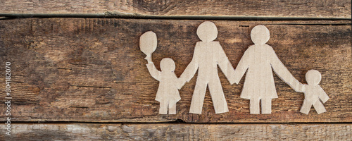 Obraz na plátně  Family with two children, paper figures on wooden background