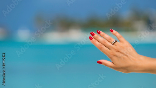 Photo  Close up of woman finger showing engagement ring on the tropical beach