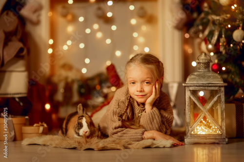Obraz Happy little girl with brown rabbit at Christmas eve - fototapety do salonu