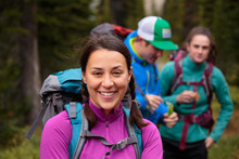Three Backpackers Take A Break While Hiking Along The Siyeh Pass Trail In Glacier National Park In Autumn.
