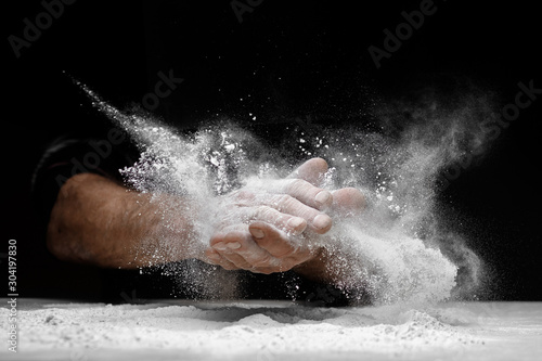 Vászonkép Chef clap white flour dust man hand on black background