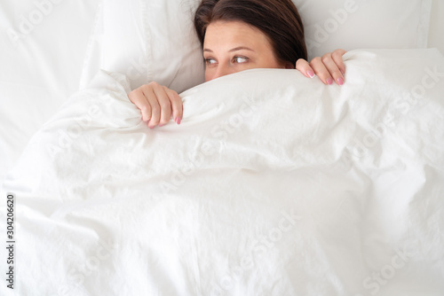 woman in bed looking surprised from under blanket Canvas Print