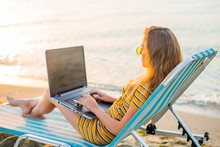 Fit Young Woman Sitting On Deck Chair At Sea View Beach Using Laptop. Female Freelance Programmer In Chaise-long Lounge Working Coding Surfing On Notebook Computer, Blank Screen. Remote Work Concept.