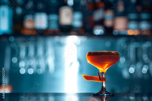 glass of fresh orange cocktail on blue background