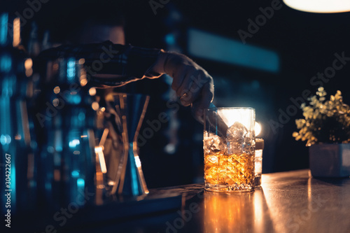 Fotomural  barman preparing cocktail on blue background in club
