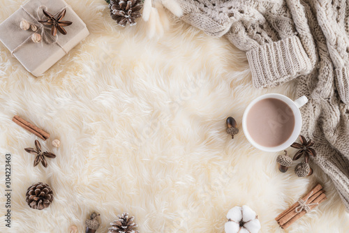 Fototapeta Autumn or winter composition. Gift box Coffee cup, cinnamon sticks, anise stars, beige sweater with knitted blanket on cream color gray fluffy background. Flat lay top view copy space. obraz