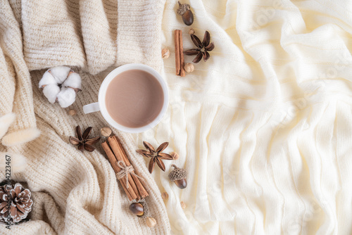 Obraz Autumn or winter composition. Coffee cup, cinnamon sticks, anise stars, beige sweater on cream color knitted blanket background. Flat lay top view copy space. - fototapety do salonu