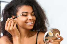 Beautiful African-American Woman Applying Makeup At Home