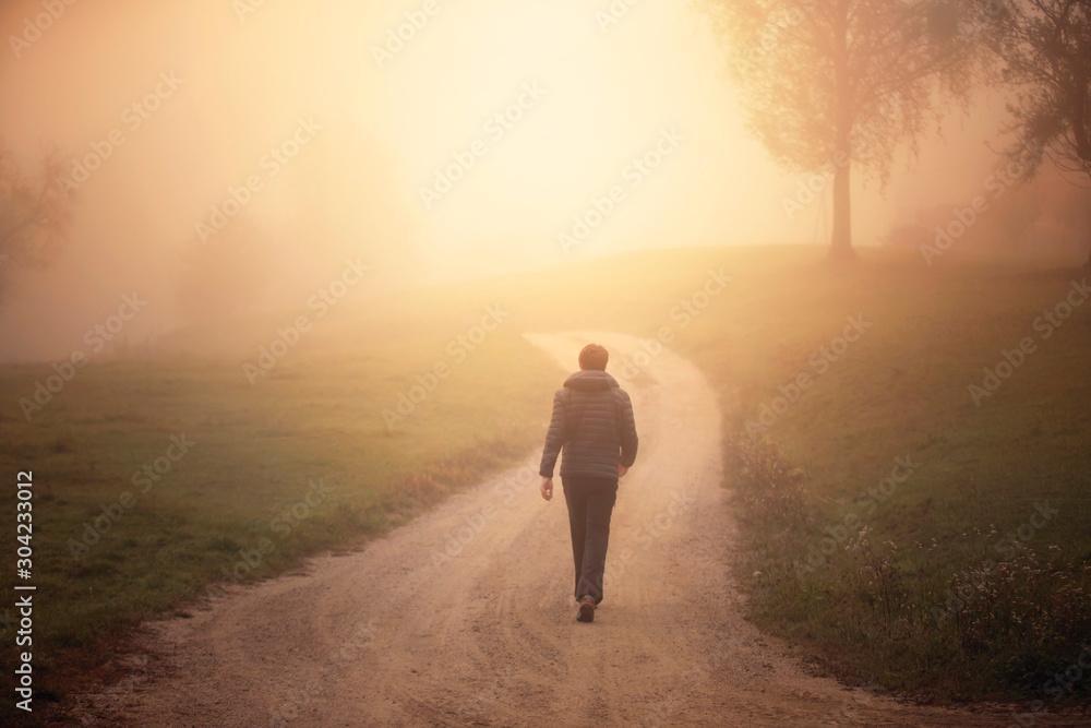 Fototapety, obrazy: Man walking alone on morning rural misty road.