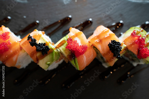 Fototapeta Top View of Sushi Roll with Salmon and Avocado on Top in Dark Tone / Japanese Food obraz
