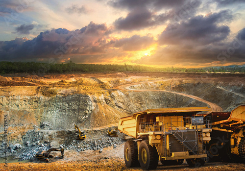 Fototapeta Yellow dump truck loading minerals copper, silver, gold, and other  at mining quarry