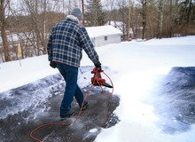 A Home Owner Uses A Leaf Blower To Remove A Light Powdery Snow Before It Turns To Ice On His Driveway