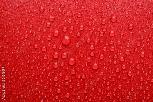 Water drops on red background, top view