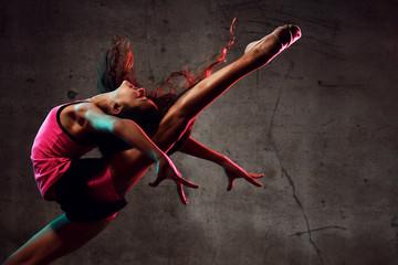 Djevojčica sa uličnog plesa skačući plešući u neonskom svjetlu radeći gimnastičke vježbe