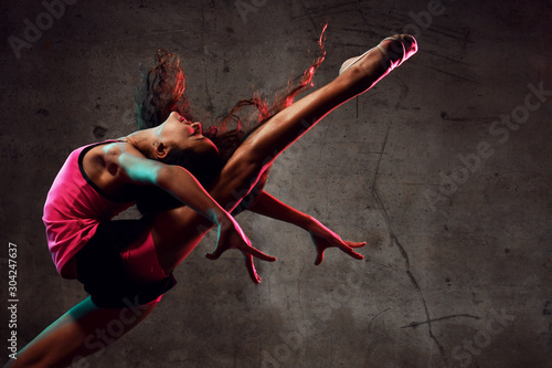 Street dance girl dancer jumping up dancing in neon light doing gymnastic exercises