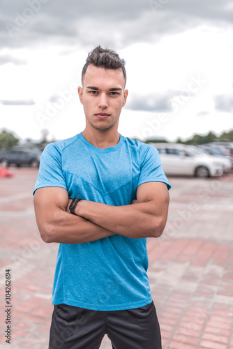 Fototapeta Leader male athlete strong, stands in summer in the city, posing. Fitness workout coach, active lifestyle of modern youth, sportswear t-shirt shorts. Motivation for life. obraz na płótnie