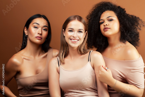 Leinwand Poster  young pretty asian, caucasian, afro woman posing cheerful together on brown back