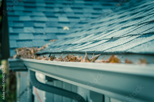 Shallow DOF clogged gutter near roof shingles of residential house full of dried Canvas Print