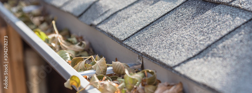 Panoramic view gutter full of dried leaves near roof shingles with satellite dis Canvas-taulu