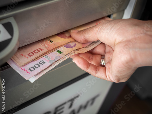 Hand receiving cash money from ATM machine. Fototapeta