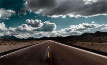 Long Straight Deserted Road To Nowhere In The Middle Of The Desert Surrounded By Mountains