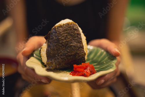 Big onigiri with seaweed serve with red pickles on leaf shape dish by lady hands Canvas Print
