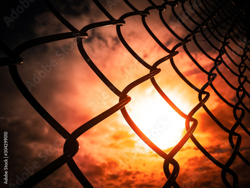 Pinturas sobre lienzo  The sunset and red sky be hide metal-chain link fencing