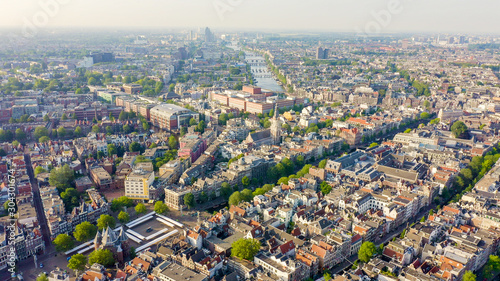 Obraz Amsterdam, Netherlands. Flying over the city rooftops towards Amsterdam Central Station ( Amsterdam Centraal ), Aerial View - fototapety do salonu